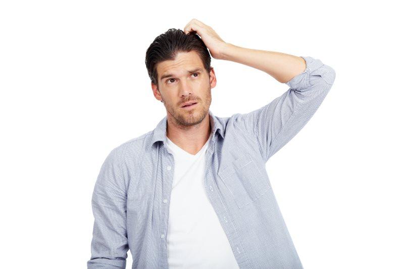 Man scratching head, looking confused